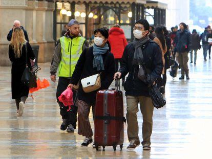 Turistas caminan en Milán, Italia, con mascarillas, este lunes.