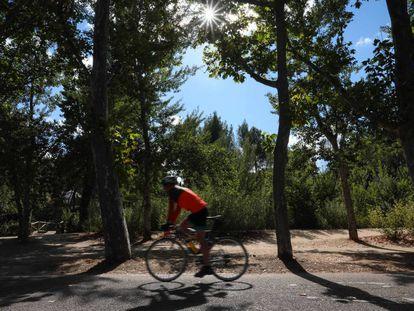 Un joven monta en bicicleta en la Casa de Campo, en Madrid.