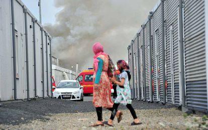 Dos refugiadas caminan frente a un centro de acogida de asilados en Kassel (Alemania) donde se produjo un incendio accidental este domingo.