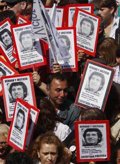 Asistentes a las exequias, con carteles con la imagen de Jara.