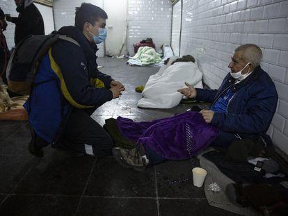 Una trabajadora del Samur Social conversa con una de las personas sin techo refugiadas en la Estación del Arte.