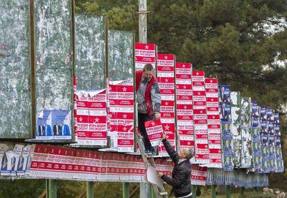 Dos hombres colocan carteles electorales en el centro de Chisinau.