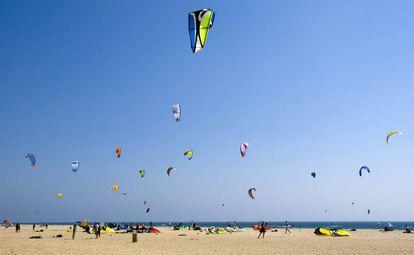Un grupo de bañistas hacen volar sus cometas en la playa de Tarifa, Cádiz.