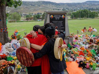 Miembros de la comunidad Mosakahiken Cree Nation se abrazan frente a un monumento en homenaje a las 215 tumbas de niños halladas en el antiguo internado Kamloops para indígenas en Columbia Británica, Canadá, el pasado 4 de junio.