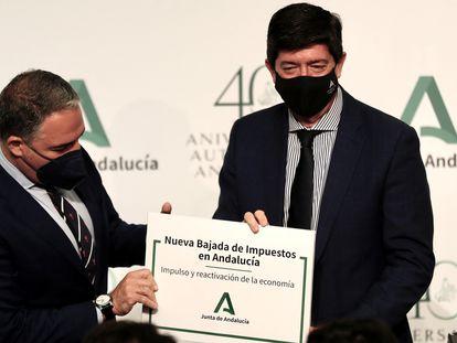 El portavoz de la Junta de Andalucía, Elías Bendodo, y el vicepresidente, Juan Marín, posan junto a un cartel que anuncia una bajada de impuestos en la comunidad, este martes.