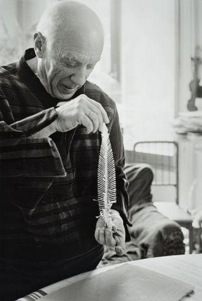 Picasso con una espina de lenguado, antes de realizar un impresión en barro para aplicarlo a una de sus cerámicas.
