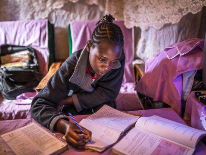 Sheila Achieng, una joven estudiante del asentamiento informal de Kibera, en Kenia, haciendo los deberes.