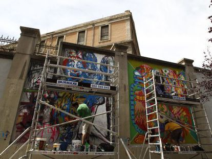 Dos artistas gráficos pintan los muros externos del espacio autogestionado de Tabacalera.