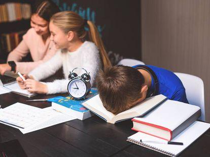 Un alumno duerme sobre un libro en una biblioteca.