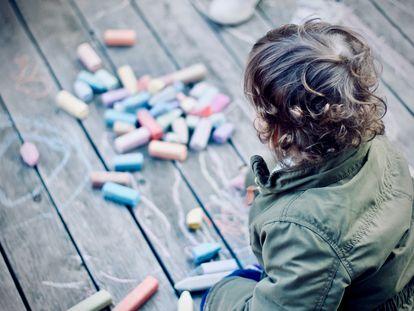 Un niño dibuja con tizas en el suelo.
