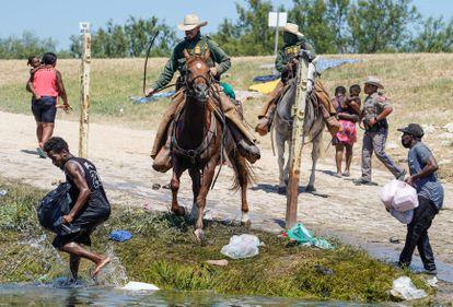 Un agente de la Patrulla Fronteriza persigue a un inmigrante haitiano cerca del campamento de Del Río, Texas, este domingo.