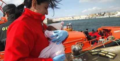 Una integrante de Cruz Roja sostiene a un bebé rescatado de una patera a principios de enero y trasladado a Tarifa.