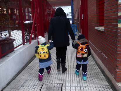 Dos alumnos llegan al colegio Arcangel Rafael, en Madrid, el 20 de enero.