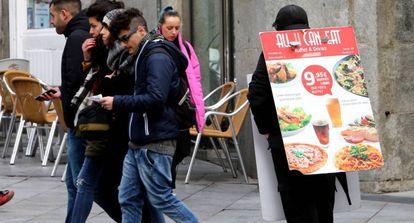 Una persona anuncia un restaurante en el centro de Madrid.