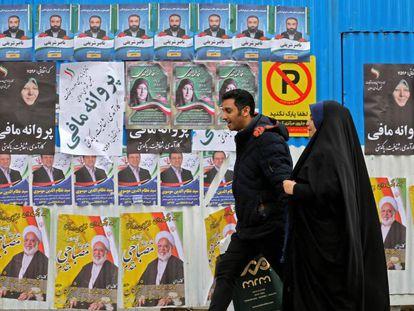 Una pareja iraní camina junto a  una pared con propaganda electoral.