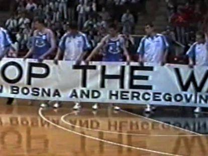 Los jugadores de la selección bosnia de baloncesto muestran una pancarta para pedir el fin de la guerra en su país, en Bolonia en 1993, en una captura del documental 'The long shot'.