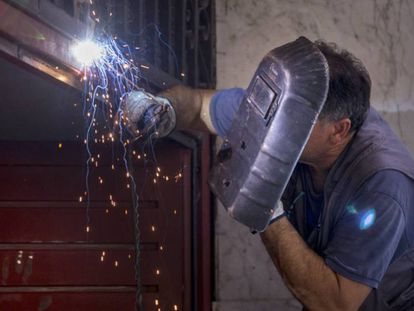 Un soldador repara una puerta de una cochera en Sevilla.