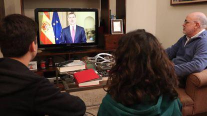 Una familia sevillana sigue el discurso de Felipe VI este miércoles.