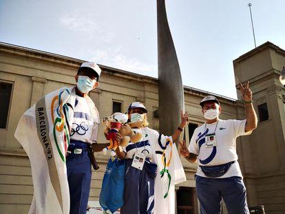 Tres antiguos voluntarios junto al pebetero el pasado 25 de julio