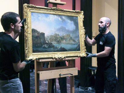 Dos trabajadores del Museo de Bellas Artes de Bilbao cuelgan el cuadro 'Vista de Bermeo. 1783', de Luis Paret y Álcazar.