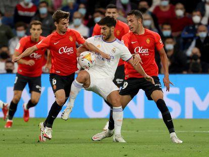 Marco Asensio (c), disputa el balón ante los jugadores del Mallorca, Aleix Febas (i) y Josep Gaya.