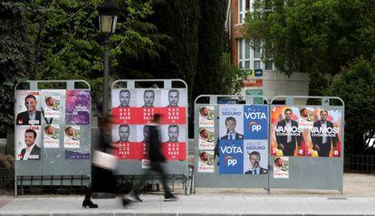 Dos personas caminan ante varios carteles electorales, durante la última campaña para las generales.