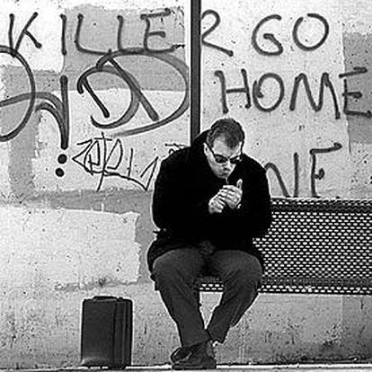 Un ciudadano de Atenas enciende un cigarrillo en una parada de autobús del centro de la ciudad.
