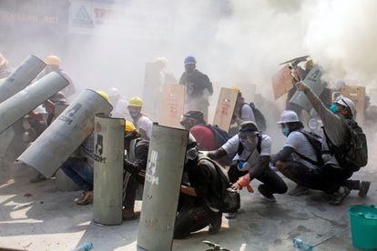 Manifestantes se protegen durante los enfrentamientos con la policía, en Yangón (Myanmar), este domingo.