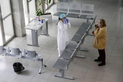Una sanitaria hace el primer cribado y reparte mascarillas en el hall de entrada del Centro de Salud Calesas en Usera en Madrid.