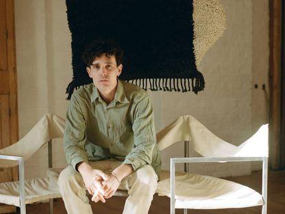 Jermaine Gallacher posa sentado en un banco de Lukas Gschwandtner, delante de su Wavy rug, en negro y crema, una tarde de febrero. |