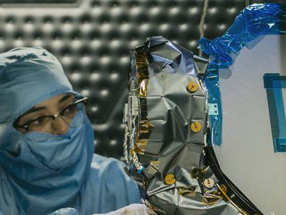 Una ingeniera trabaja en un satélite.