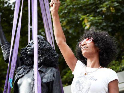 La activista antirracista Jen Reid posa con su estatua. En vídeo, la historia de la estatua crada por el artista Mar Quinn.