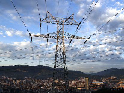 Una torre de transporte de energía perteneciente a red eléctrica, con la ciudad de Bilbao al fondo.