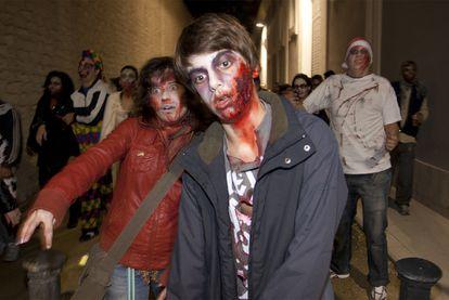 Participantes en la <i>Zombie Walk</i> de Alicante a su paso por un callejón.