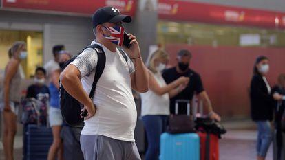 Un viajero habla por teléfono mientras espera la información de su vuelo de vuelta al Reino Unido, el 26 de julio en el aeropuerto de Tenerife.