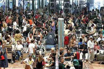 Cientos de pasajeros esperan sus vuelos ayer en el aeropuerto de El Prat de Barcelona.