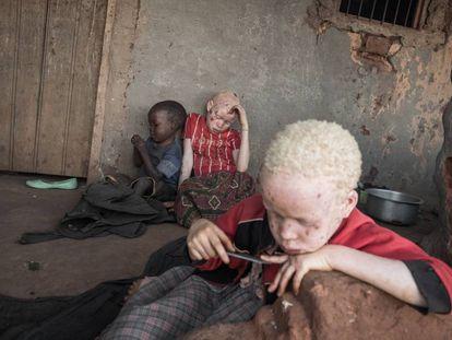 Suema, de nueve años (centro), su hermana pequeña Moamina, de seis (derecha), y su hermano menor Rashid, de tres (izquierda), sentados en el porche de su casa.