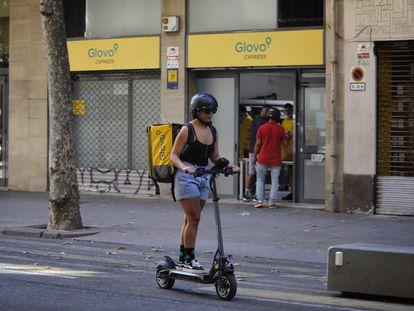 Una repartidora de Glovo, frente a un supermercado de la compañía de reparto en Barcelona.