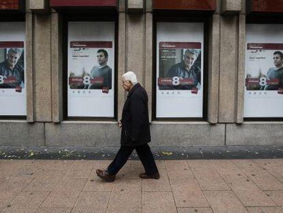 Un hombre pasa frente a anuncios de planes de pensiones de un banco
