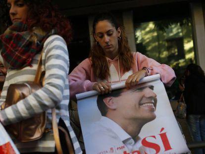 Una simpatizante enrolla un póster de Pedro Sánchez este sábado.