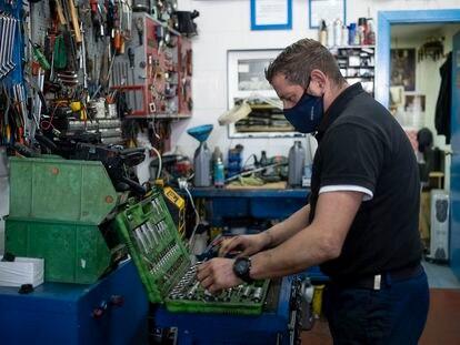 Un mecánico de automóviles trabaja en su taller de Sevilla.