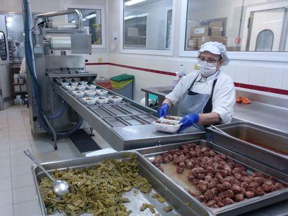 Una mujer prepara comida en un servicio de cátering.