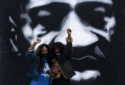 Dos mujeres negras levantan el puño ante un mural de George Floyd en Minneapolis, el pasado octubre.