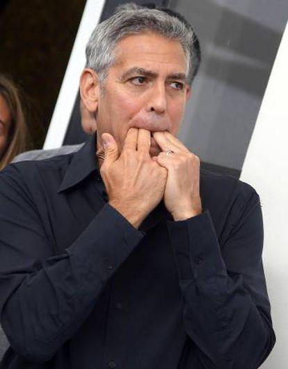 George Clooney silba en el posado ante los fotógrafos en Venecia.