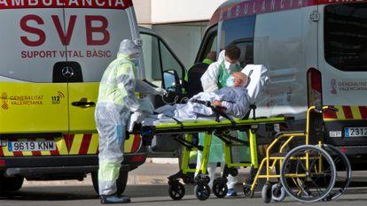 Sanitarios en Urgencias trasladan enfermos desde las ambulancias al Hospital de La Fe de València, que ya ha empezado a derivar pacientes con covid-19 al hospital de campaña..