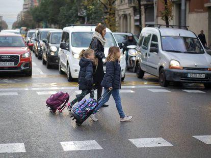 Varias personas cruzan un paso de peatones en la transitada calle Aragó de Barcelona