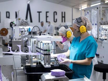 Trabajadores que fabrican mascarillas en una 'start-up' creada durante la pandemia de la covid-19, en Castellón.