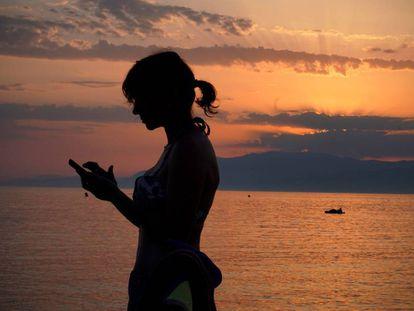 Una mujer revisa su teléfono móvil en la playa de Cabo de Gata, en Almería.