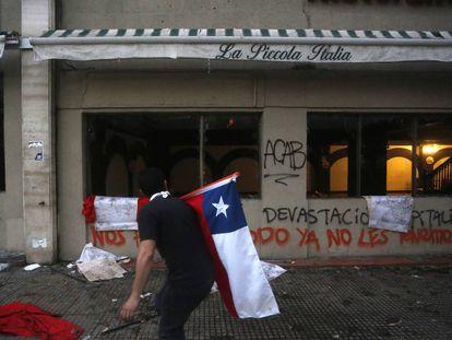 Un manifestante camina frente a un restaurante cerrado en Santiago de Chile.