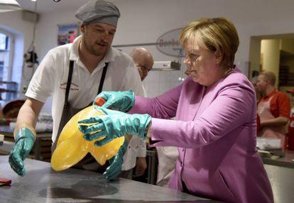 La canciller alemana, Angela Merkel, amasa una pasta de limón dulce en una repostería en Eckernfoerde, al norte de Alemania, a dos días de las elecciones en Schleswig-Holstein.